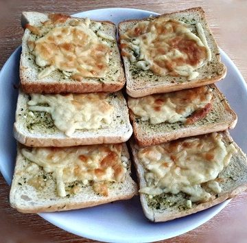 A recipe of a homemade garlic bread using a white sliced bread with mozzarella and cheddar cheese