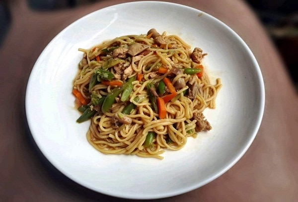 A filipino egg noodle dish called Pancit Canton which is mixed with chicken and vegetables.