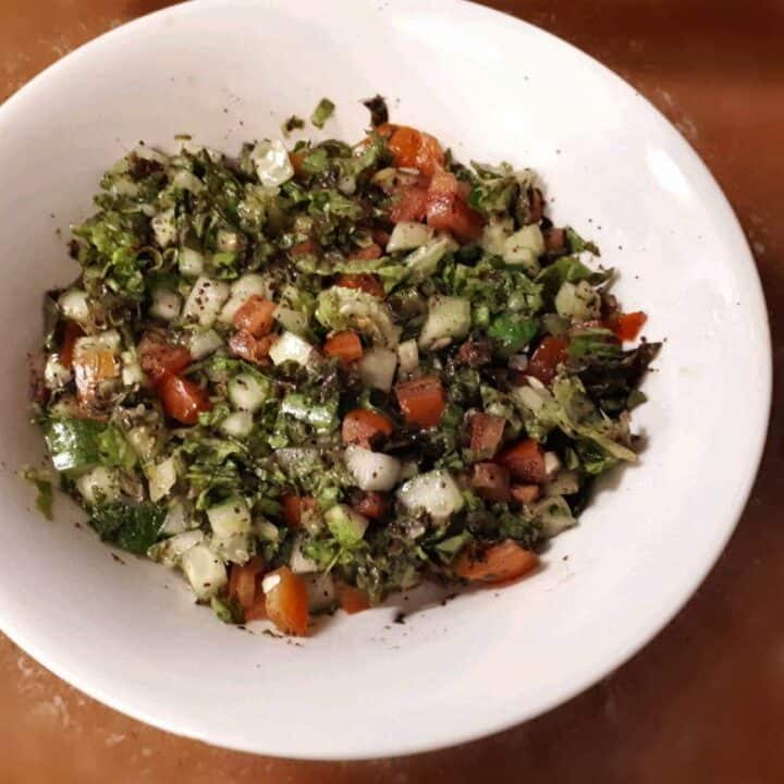 Arabic Salad Recipe mixed with cucumber, tomatoes, lettuce and parsley in a large bowl