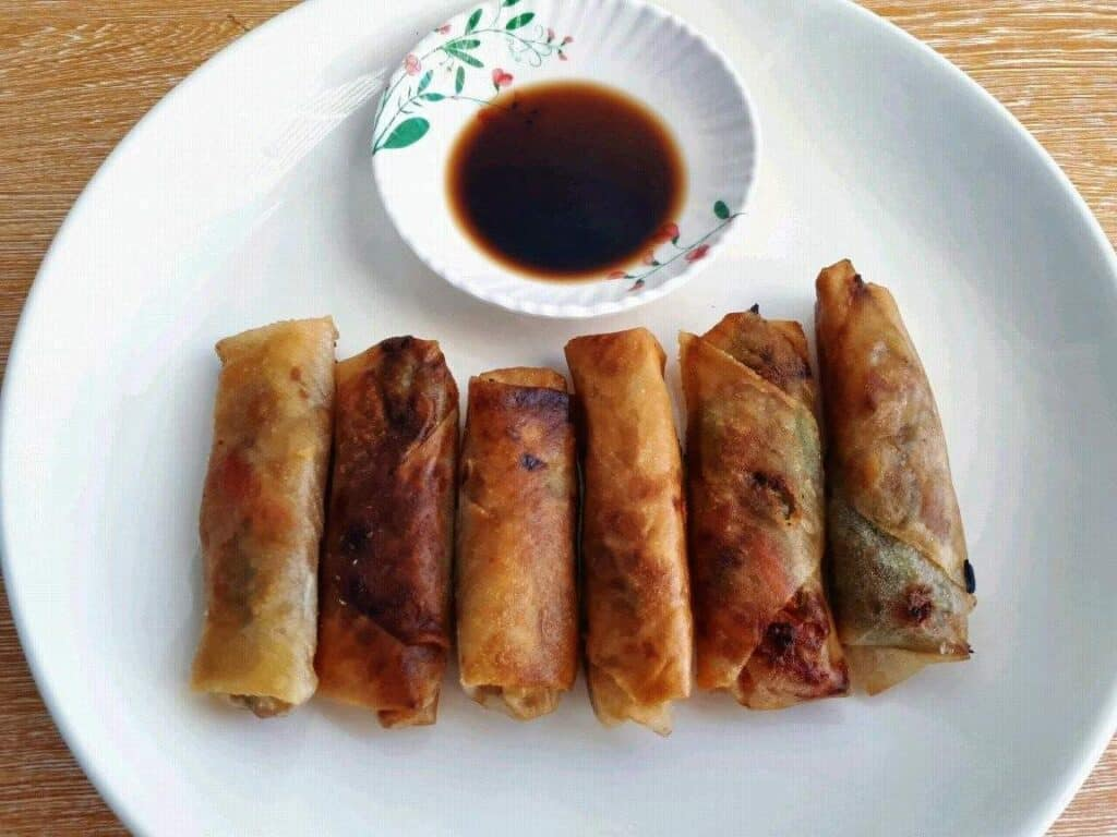 Vegetable Lumpia served with Vinegar Soy Sauce in a plate