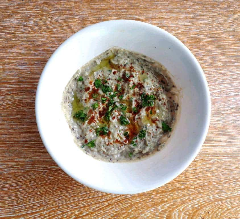 Aubergine Dip (Baba Ganoush) garnished with paprika and chopped parsley and drizzle with olive oil.
