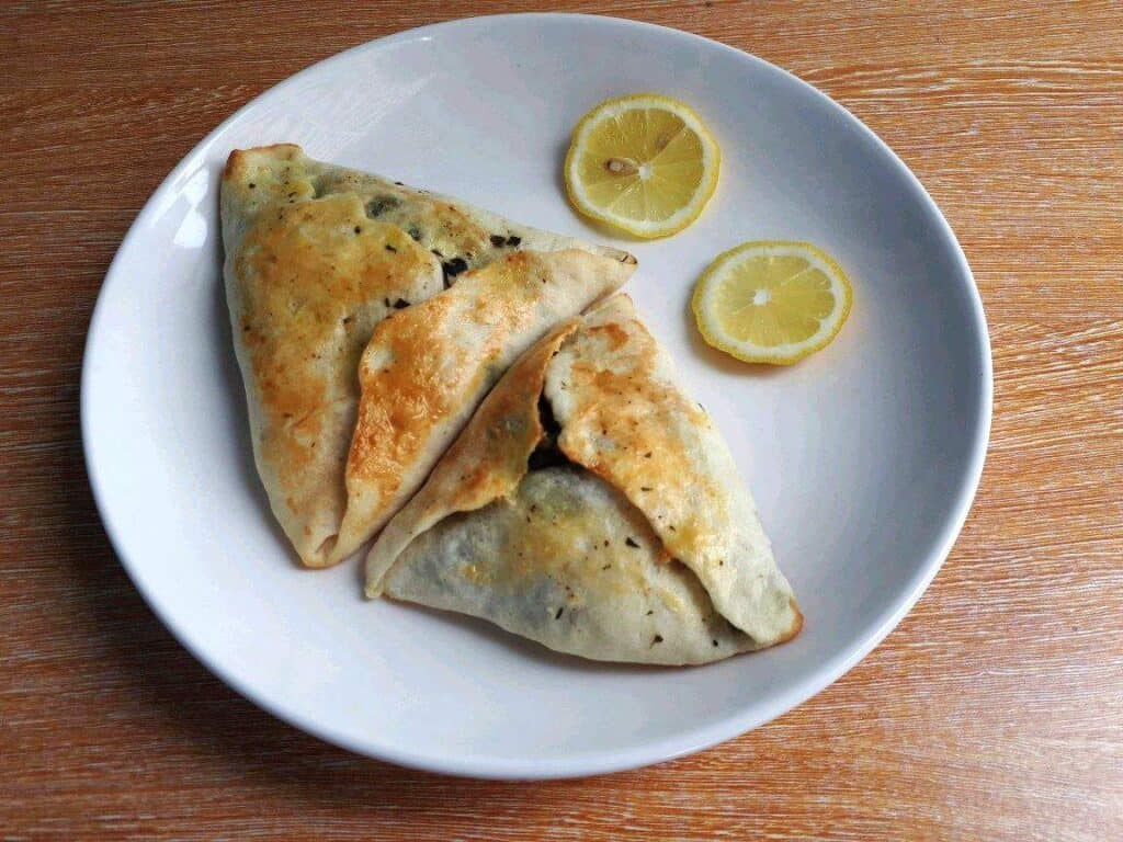 Sabanekh Spinach Fatayer Recipe serve with slices of lemon in a plate