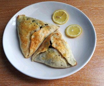 Sabanekh Spinach Fatayer Recipe serve with two slices of lemon in a plate