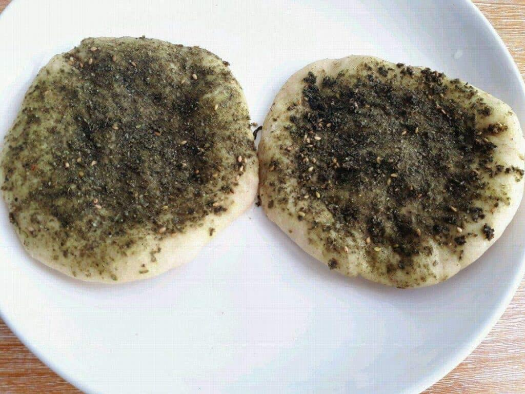 A Lebanese Zaatar Bread (Zaatar Manakish Recipe) top with Zaatar spices in a plate.
