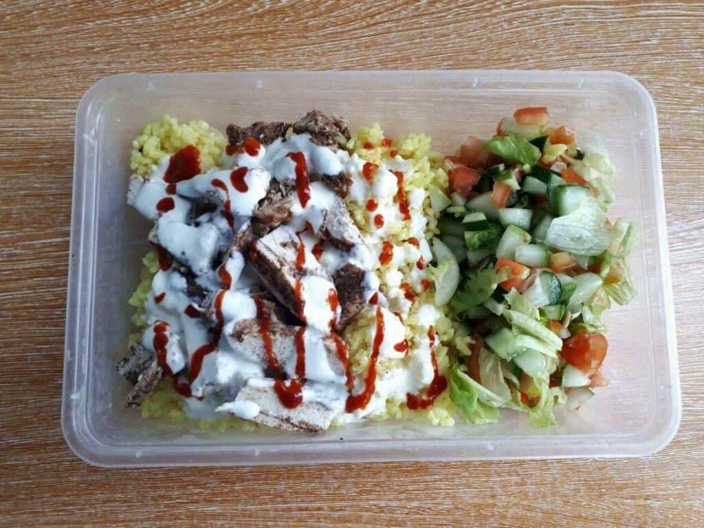 Chicken Shawarma Rice with raw vegetables, and chopped chicken drizzle with white yogurt garlic sauce  serve in a container