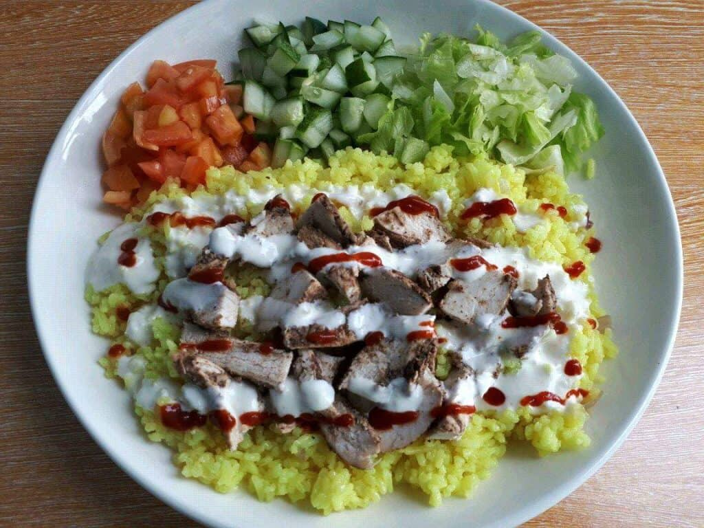Chicken Shawarma Rice recipe with raw vegetables, and chopped chicken drizzle with white yogurt garlic sauce  serve in a plate.
