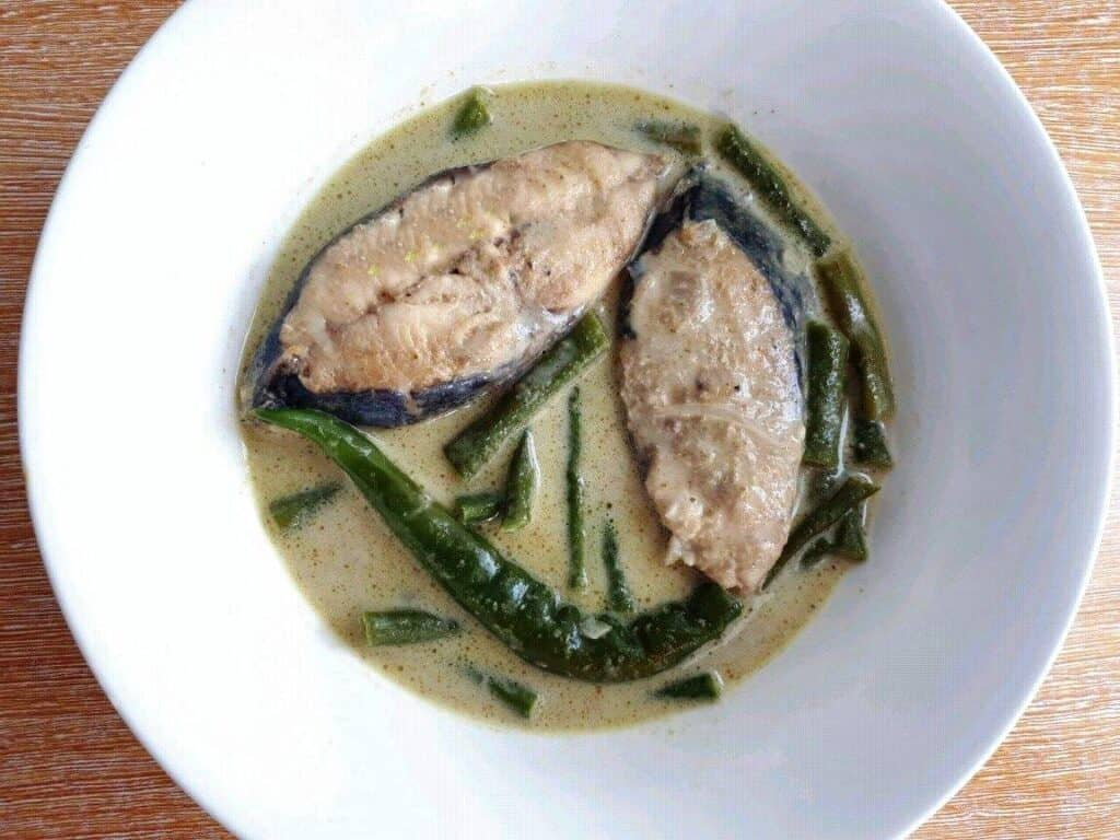 Thai Fish Green Curry with green beans and chilies in a bowl.