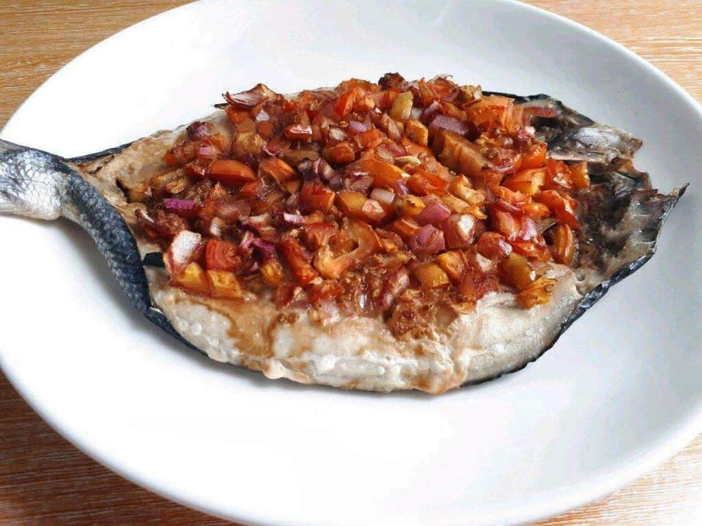 Baked Bangus (Milkfish) topped with ginger, tomatoes and red onion.