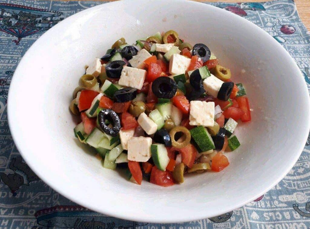 A Shepherd Salad Recipe mix with feta cheese, olives, tomatoes, and cucumber in a large bowl