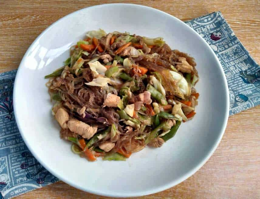 Pancit Sotanghon Guisado with vermicelli noodle, chicken breast, julienne carrots, string beans and cabbage in a plate