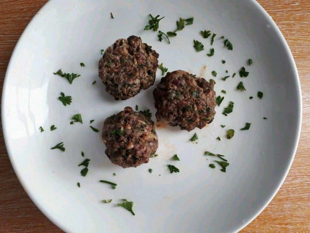 Beef Kofta kebab shaped in a meatball garnished with chopped parsley in a plate.