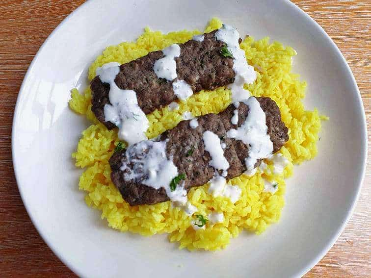 Jordanian Beef Kofta Kebab served with yellow rice, drizzle with white yogurt sauce and garnished with chopped parsley in a plate.