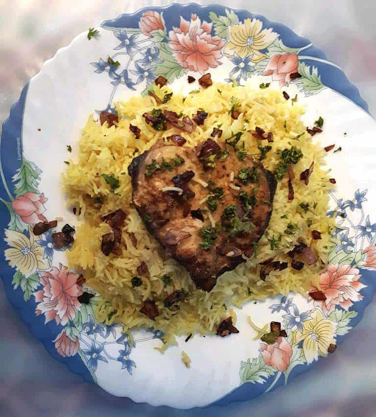 Fish Machboos mixed with turmeric basmati rice, boneless spanish mackerel fish. and garnished with fried brown onion and parsley.