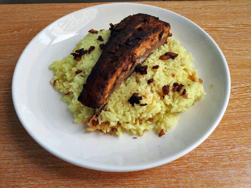 Fish Machboos mixed with turmeric basmati rice, salmon fillet, and garnished with fried brown onion