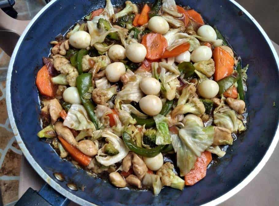 A Filipino Chop suey mixed with chopped chicken, carrot, cauliflower, broccoli, quail egg and cabbage serve in a pan