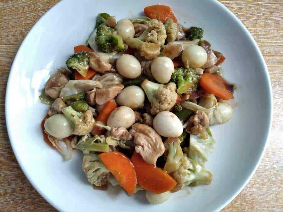 A Filipino Chop suey mixed with chopped chicken, carrot, cauliflower, broccoli, quail egg and cabbage serve in a plate