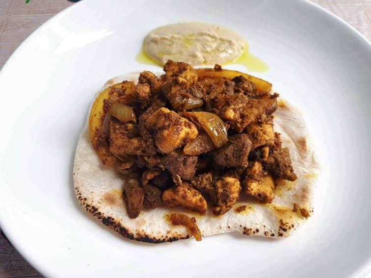 Jerusalem Mixed Grill serve above the Pita bread and serve with Hummus sauce in a plate