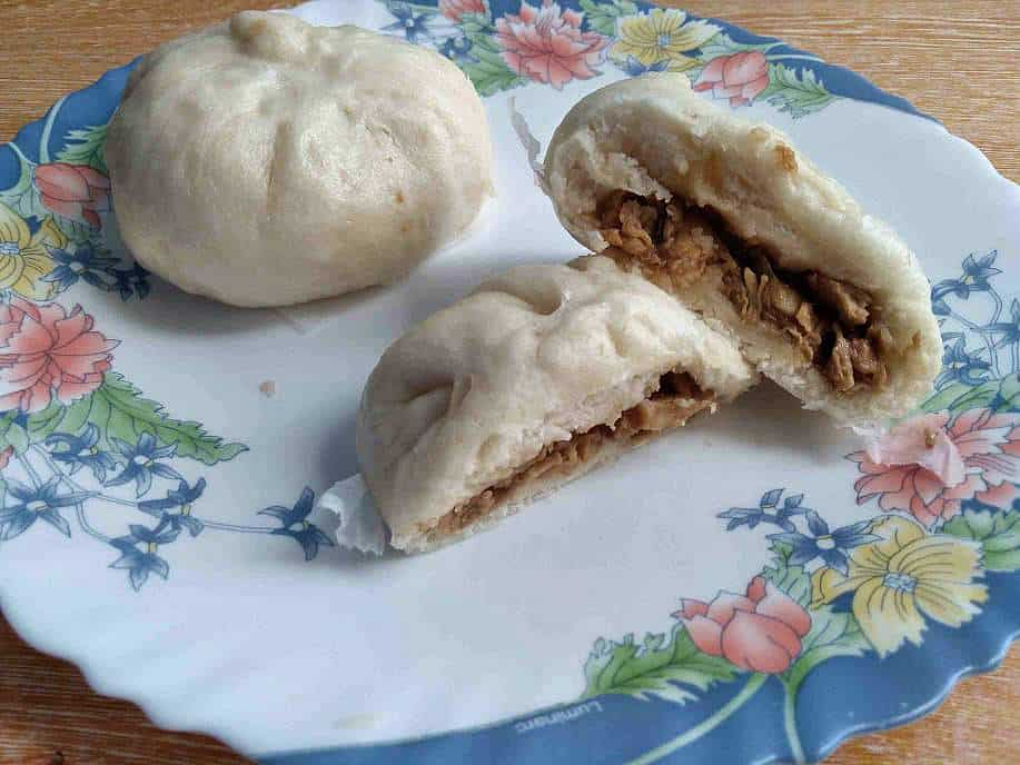 A white steamed bun filled with chicken siopao asado filling serve on a plate.