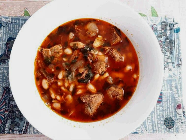 Fasolia recipe tomato red stew with white beans and beef cubes on a bowl.