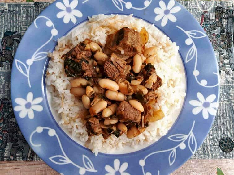 Fasolia Recipe mixed with White beans and boneless beef cubes served on a rice in a plate