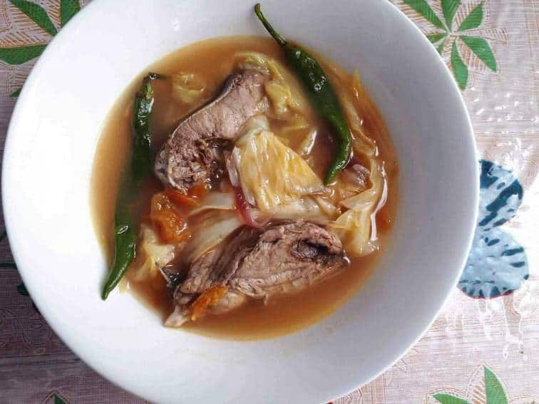 Fish Sinigang Soup Recipe mixed with boneless fish, green chilies, cabbage and tomatoes in a bowl.