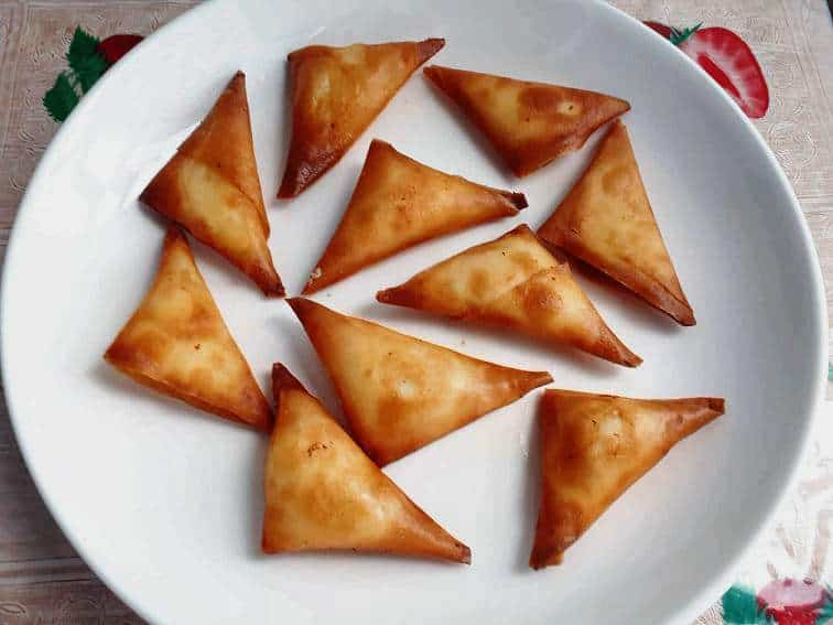 10 pieces of cheese samosas in a plate.