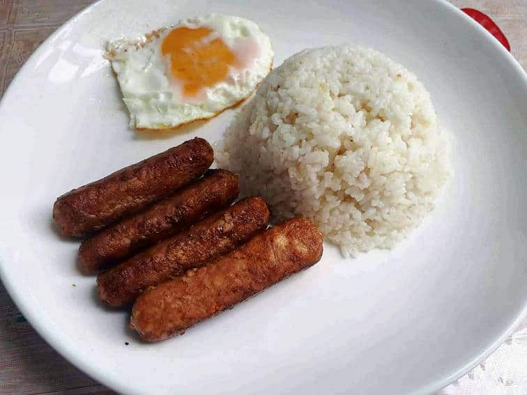 Chicken Longganisa serve with garlic white rice and fried sunny side up egg in a plate