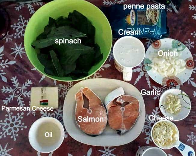 Recipe ingredients of Salmon Alfredo Pasta which includes Spinach Leaves, Parmesan & cheddar cheese, chopped onion & garlic, light cream, vegetable oil and uncooked penne pasta