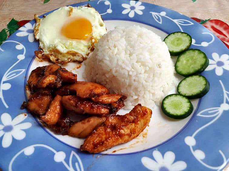 Chicken Tocino served with white rice, sunny-side up egg and sliced cucumber.