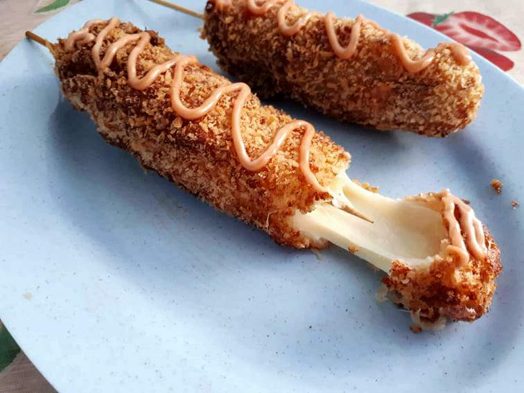 Korean Mozzarella Corn Dog with cheese that is coated in batter & breadcrumb and drizzle with mayo ketchup sauce