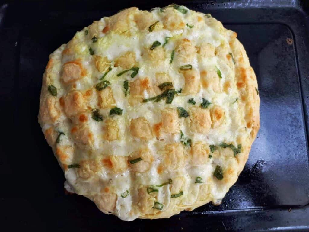 Garlic Mozzarella bread mixed with cheese and spread with garlic green onion butter in a tray.