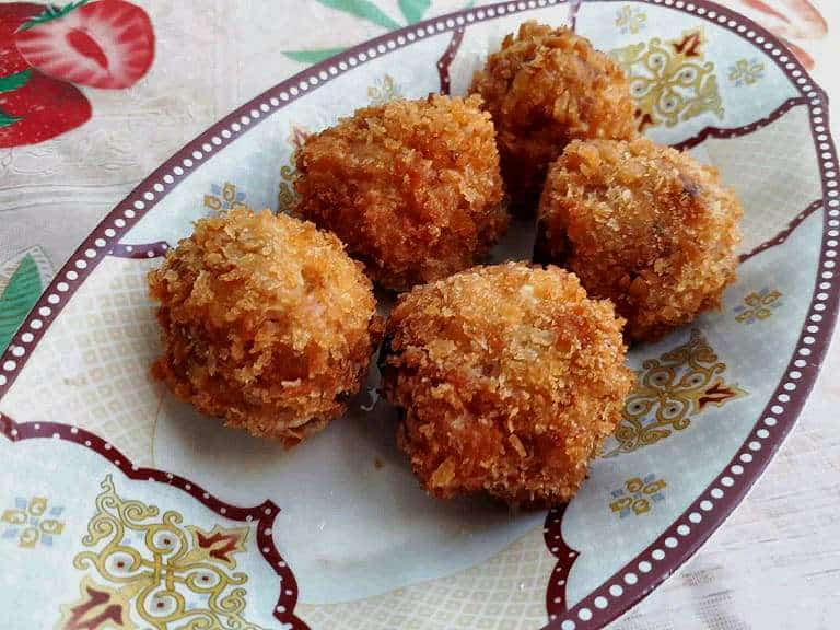 a deep fried Shrimp Croquettes in a ball shaped serve in a plate