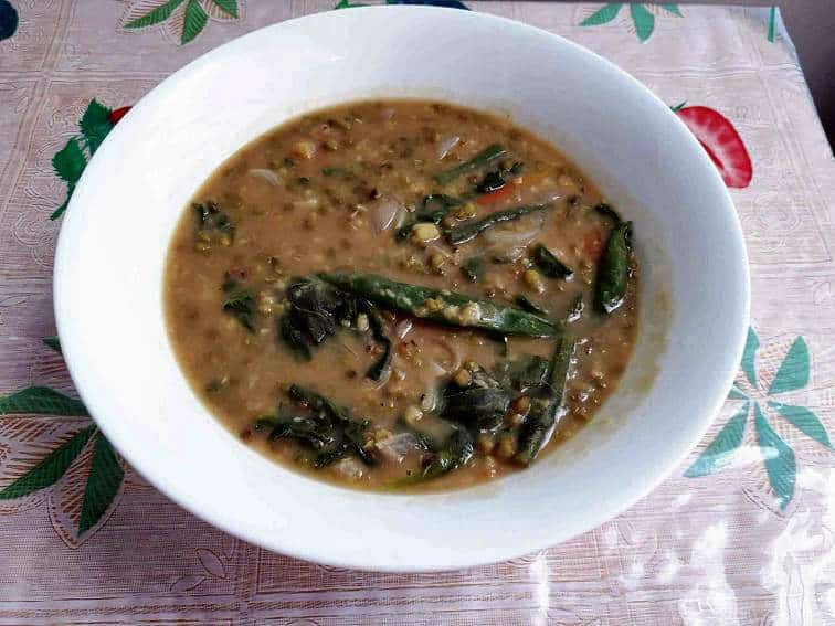 A filipino mung bean soup Ginisang Monggo mixed with spinach and green beans served in a plate bowl.