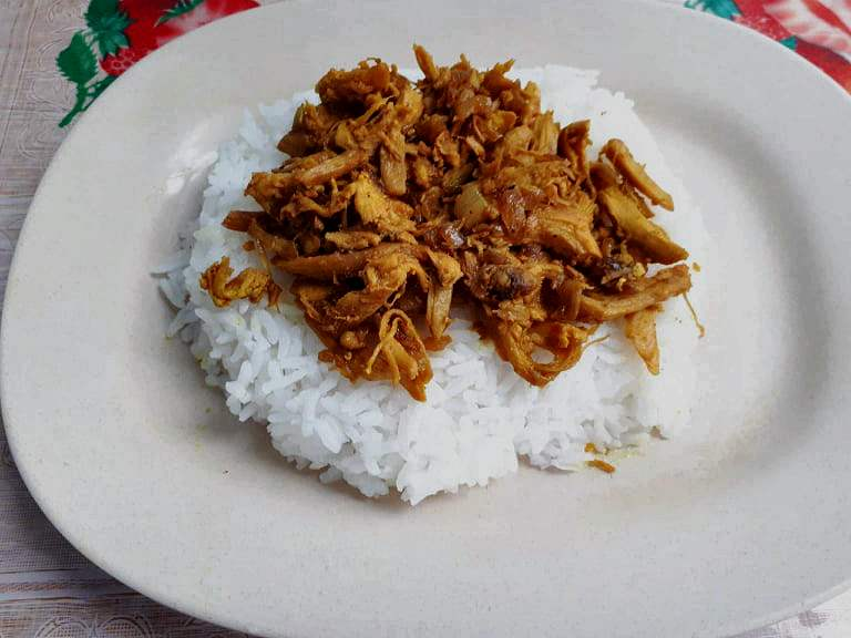 Chicken Pastil Recipe made with white steamed rice topped with dry shredded chicken serve in a plate.