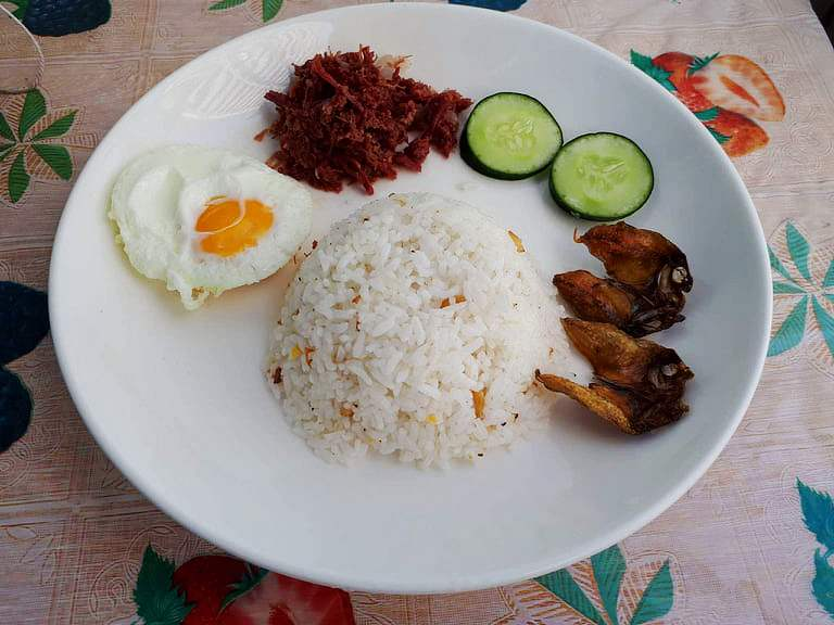 A filipino breakfast Cornsilog mixed with corned beef, garlic rice, sunny side up egg, sliced of cucumber and fried fish Danggit